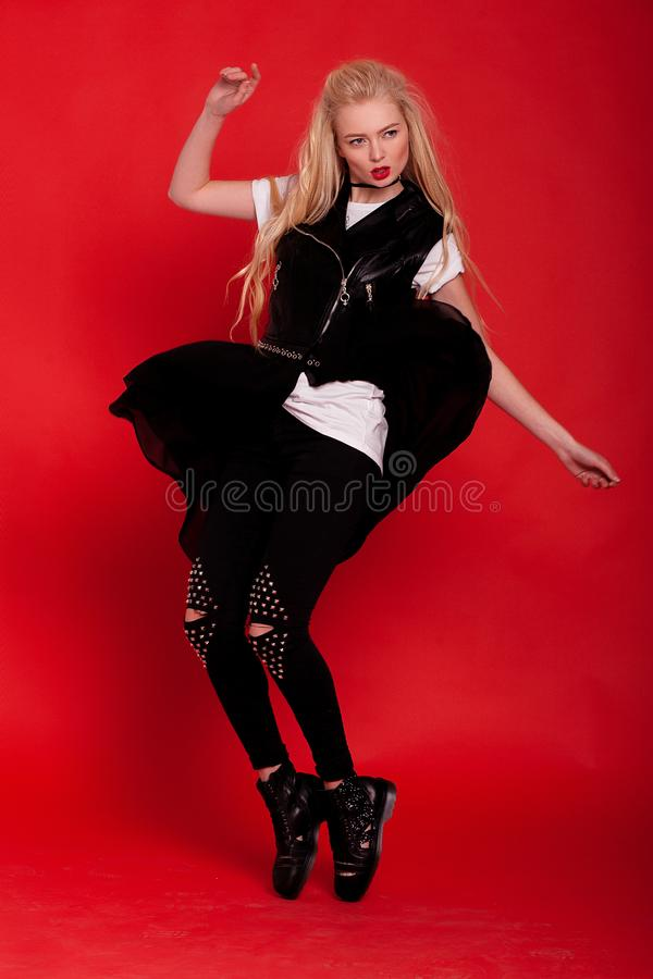 Model in black dress and boots posing on red background. stock photography