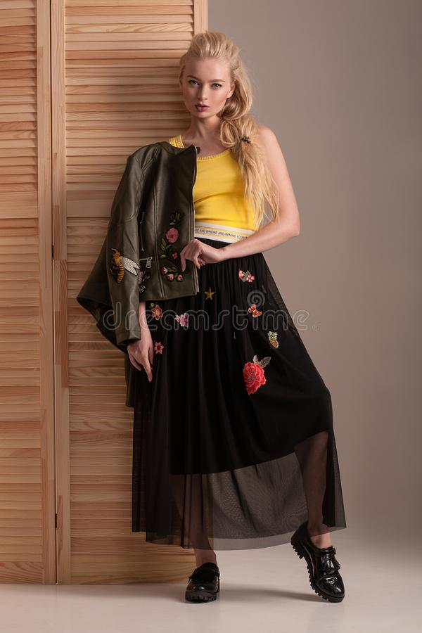 Blonde model in black skirt and jacket posing in studio. stock photography
