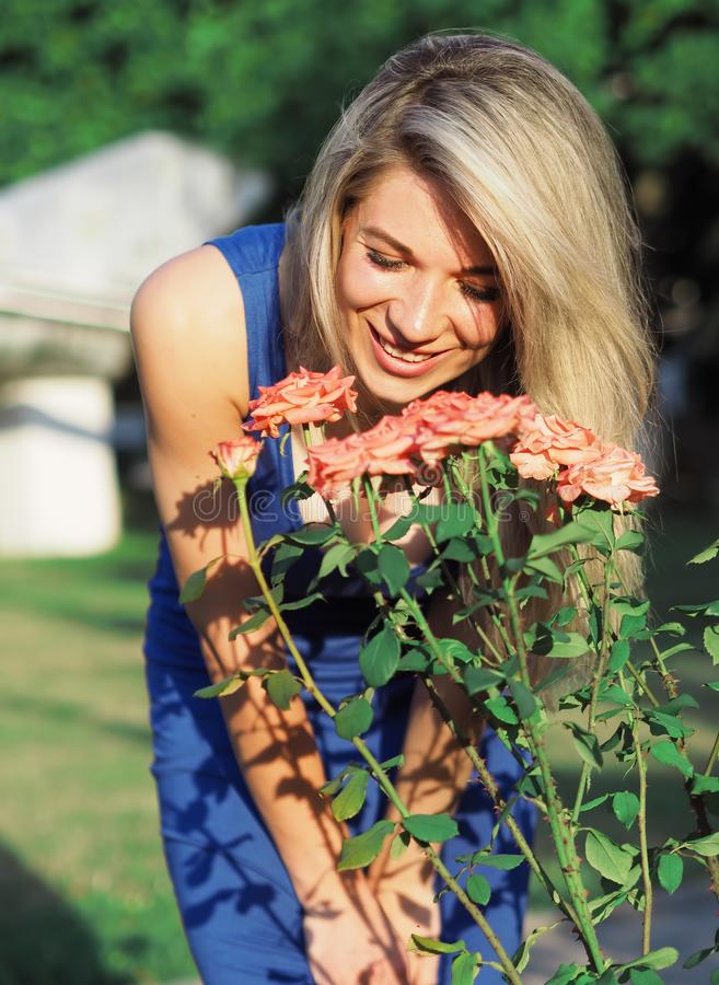 Blonde model at the bright sun posing near pink roses. The Blonde model at the bright sun posing near pink roses stock photos