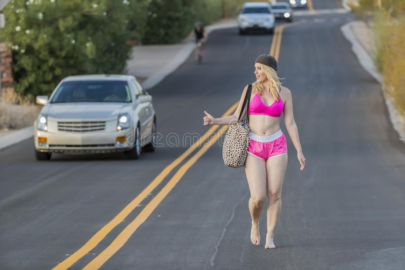 Blonde Model Hitchhiking Down A Highway stock photos