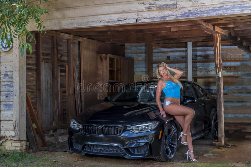 Blonde Model Posing Outdoors With A Sports Car stock photo