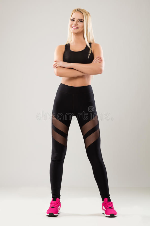 Blonde model wearing black leggins and pink trainers royalty free stock image