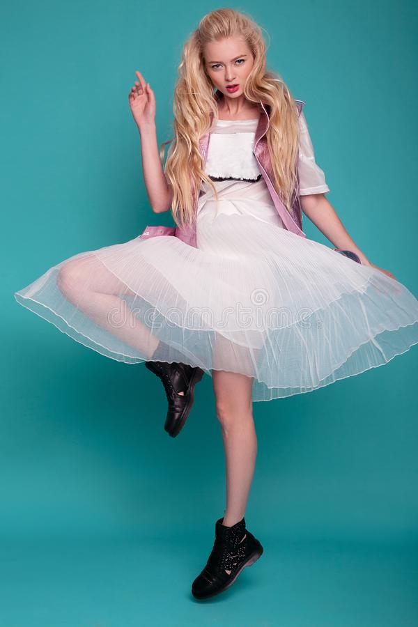 Blonde model in white dress and black boots posing on blue background. royalty free stock images