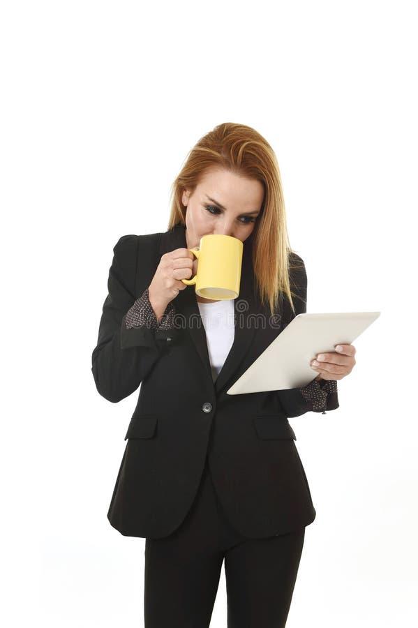 Blonde mooie onderneemster die digitale tabletstootkussen het drinken koffie houden kijkend nadenkend royalty-vrije stock afbeeldingen