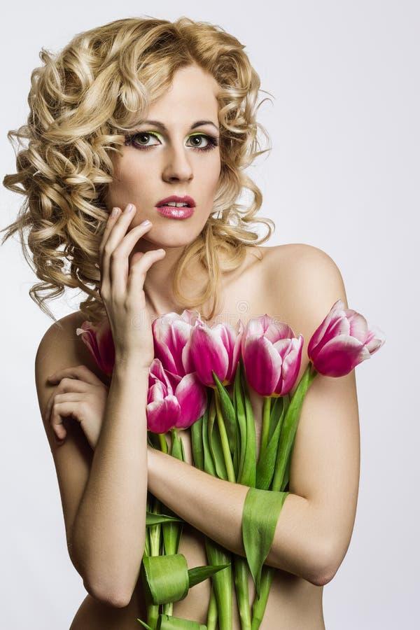 Blonde mooie vrouw met bloemen stock foto