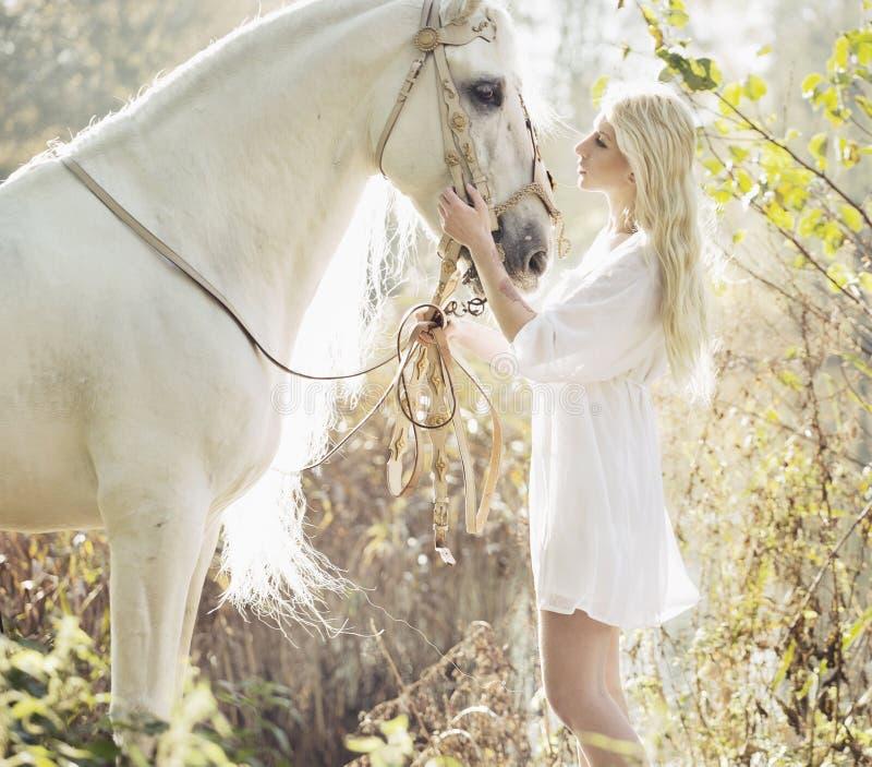Blonde mooie vrouw wat betreft mejestic paard royalty-vrije stock fotografie