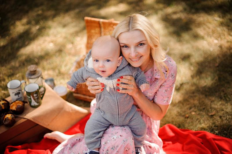 Blonde mother hugging a cute baby son royalty free stock photography