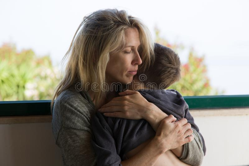 Blonde mother hugs her brunette boy with deep love stock photo