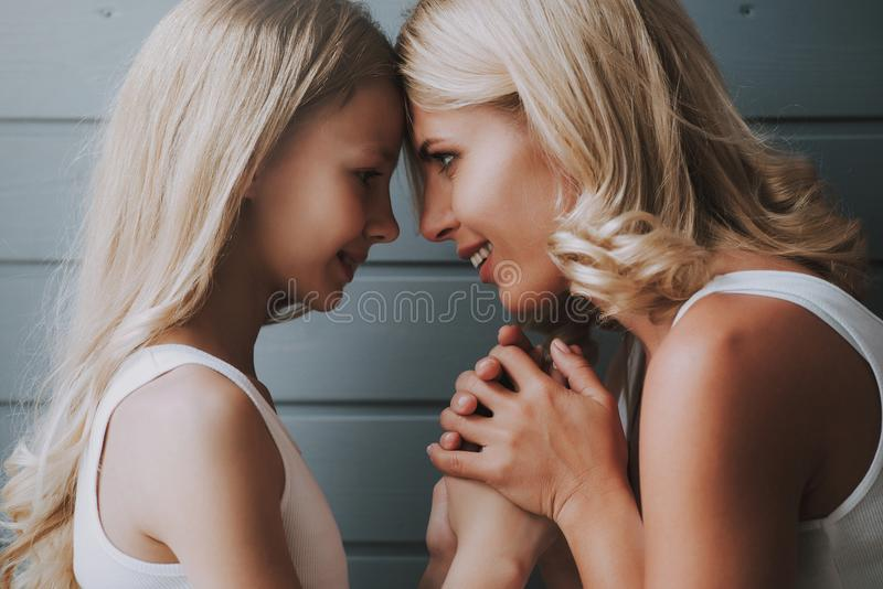 Blonde mother looks into eyes of blonde daughter, hugging hands on wooden background. royalty free stock photo