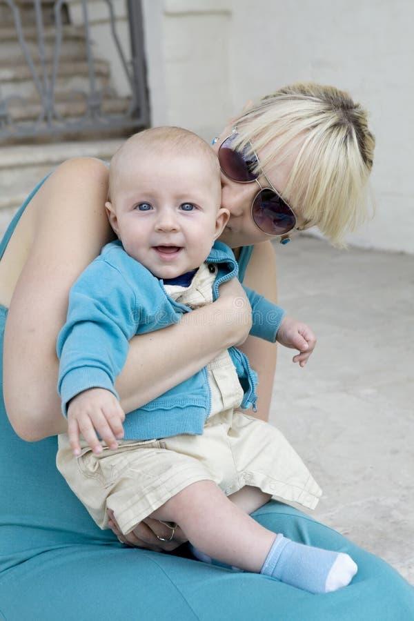 Blonde Mutterholding ihr lächelndes Schätzchen lizenzfreie stockfotos