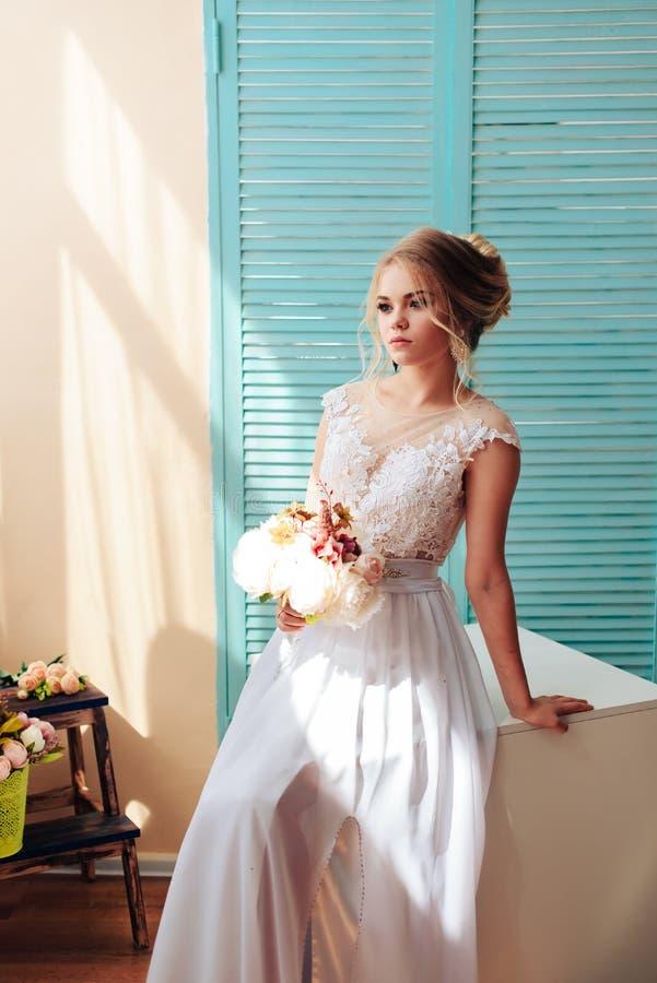 Blonde muy hermoso con los ojos azules en un vestido blanco de la novia cerca de una ventana con un ramo de flores fotografía de archivo