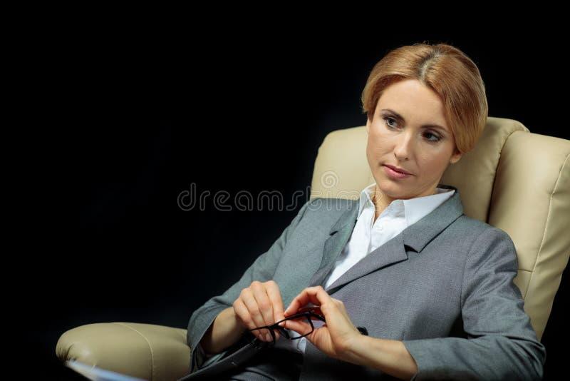 Blonde nachdenkliche Geschäftsfrau in der grauen Klage, die auf Lehnsessel sitzt stockfotografie
