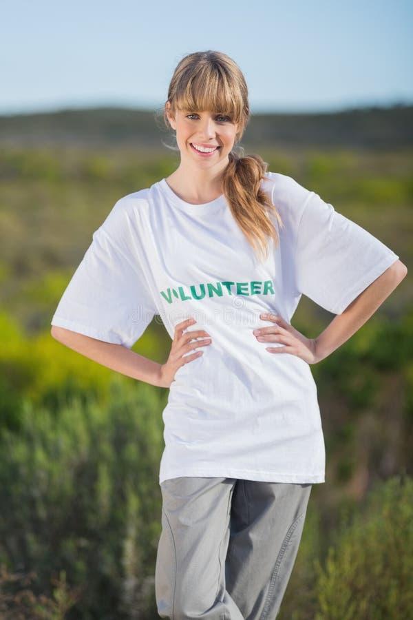 Blonde naturelle gaie utilisant un T-shirt offrant image libre de droits