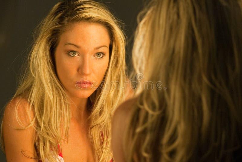 Blonde nello specchio fotografia stock