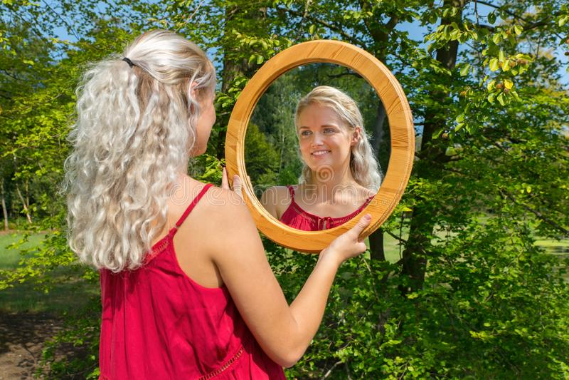 Blonde niederländische Frau betrachtet Spiegel in der Natur stockfoto