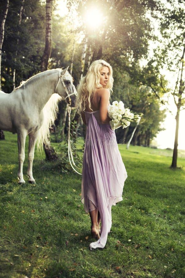 Blonde nimf met bloemen en paard stock afbeeldingen