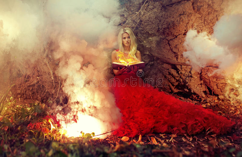 Blonde nimfholding die magisch boek in brand steken stock fotografie