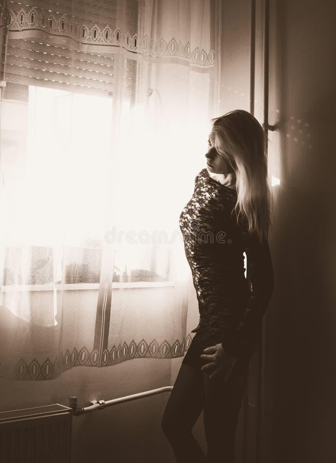 Blonde no vestido preto imagens de stock