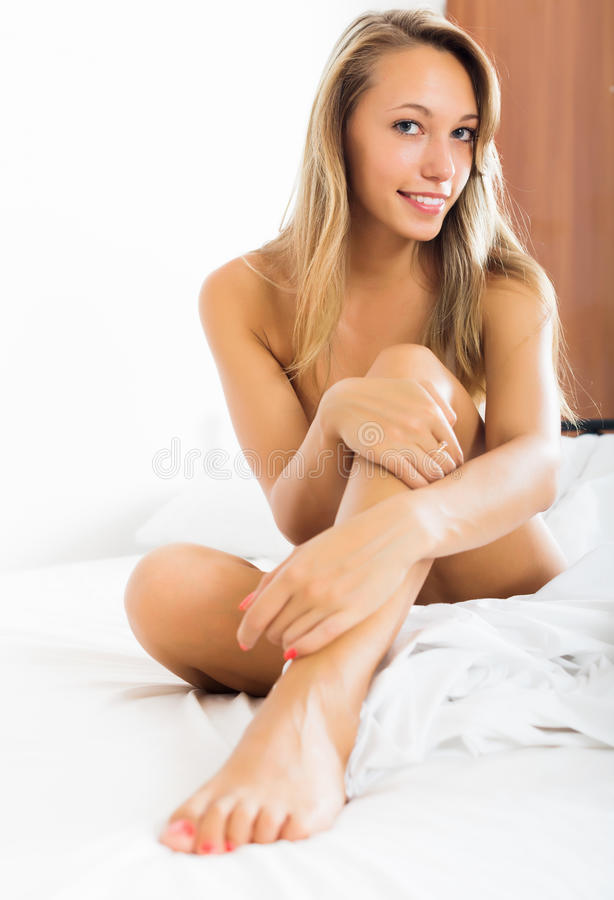 Blonde nude girl sitting on bed stock photos