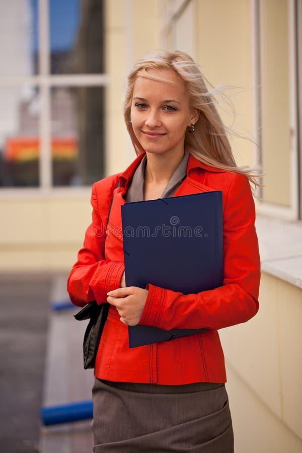 Blonde onderneemster met omslagen in openlucht stock fotografie