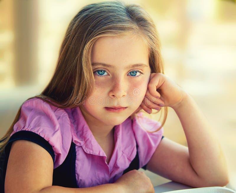 Blonde ontspannen droevige de uitdrukkings blauwe ogen van het jong geitjemeisje royalty-vrije stock fotografie