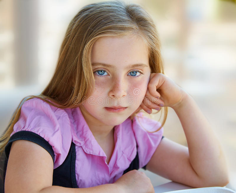 Blonde ontspannen droevige de uitdrukkings blauwe ogen van het jong geitjemeisje stock foto