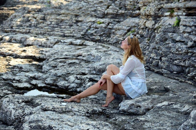 Blonde op rotsachtig strand stock foto's