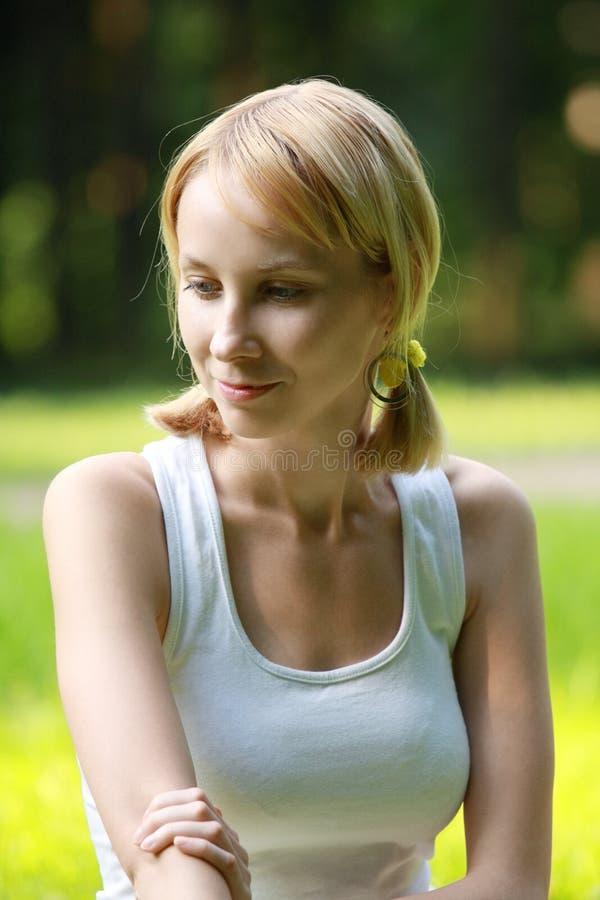 Blonde in park dat in gedachten wordt verloren stock foto