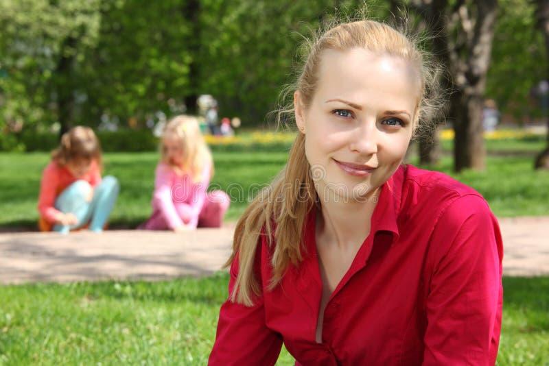 Blonde in park met speelkinderen op achtergrond stock fotografie
