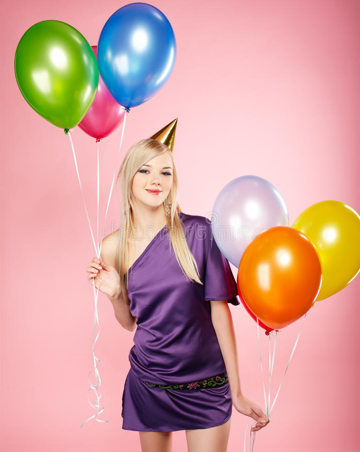 Blonde party girl. Portrait of beautiful blonde party girl with balloons on pink royalty free stock photography
