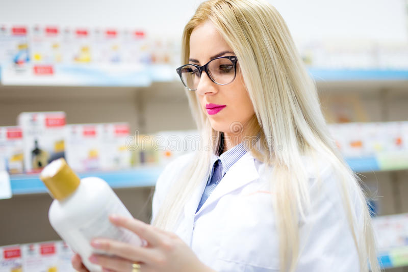 Blonde pharmacist looking at pills and creams in store. Female medical assistant reading on labels royalty free stock images