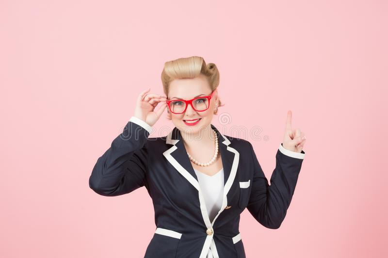 Blonde pin-up girl in blue jacket show advert place above. Female in jacket with red glasses and big smile point up by finger royalty free stock images
