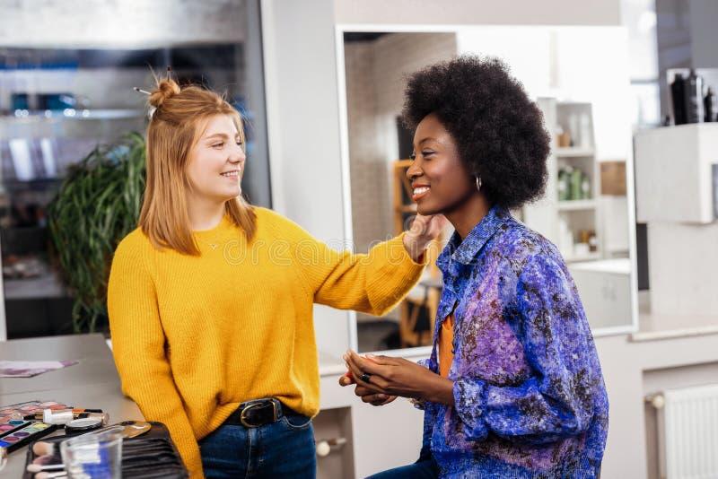 Blonde positieve stilist die make-up doen aan een Afrikaans Amerikaans model stock afbeelding