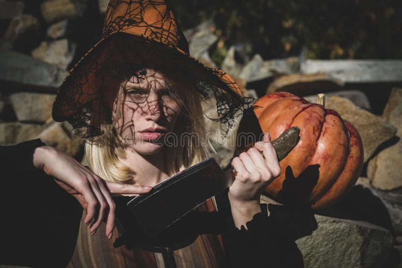 Blonde is preparing to carving a pumpkin. Witch posing with Pumpkin on wood background. Happy gothic young woman in. Witch posing with Pumpkin on wood background royalty free stock image
