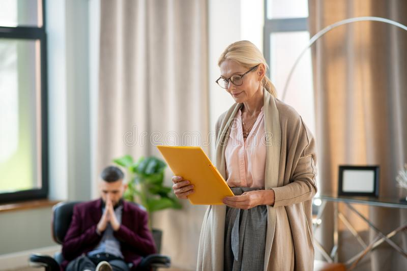 Blonde psychoanalyst wearing glasses reading info about patient. Reading info. Blonde-haired experienced psychoanalyst wearing glasses reading info about patient royalty free stock photo