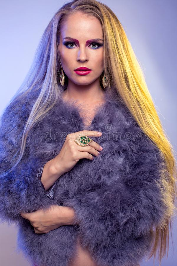 Blonde in purple fur coat with long hair. Blonde in purple fur coat stands on white background in black bodysuit, with long loose hair stock photo