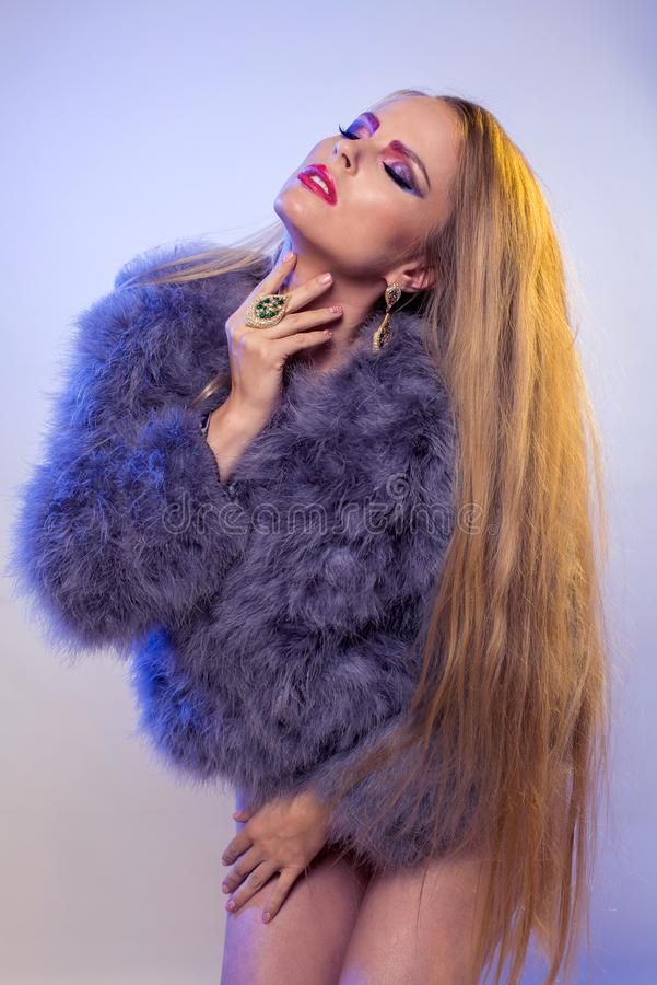 Blonde in purple fur coat with long hair. Blonde in purple fur coat stands on white background in black bodysuit, with long loose hair stock image