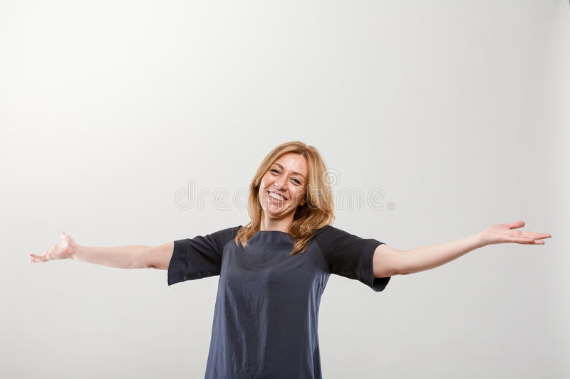 Blonde real smiling woman with open arms royalty free stock photo