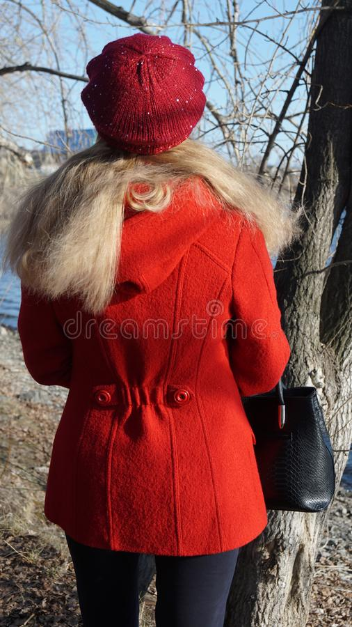Blonde in red coat and beret stands with his back to nature stock photo