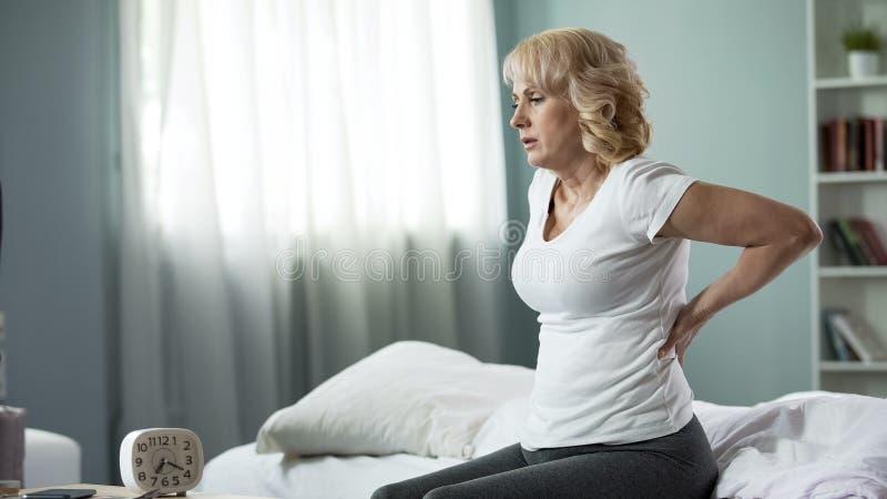 Blonde reife Dame, die auf Bett sitzt und zurück sie, Nervenwurzel-Entzündung und die Schmerz berührt stockbild