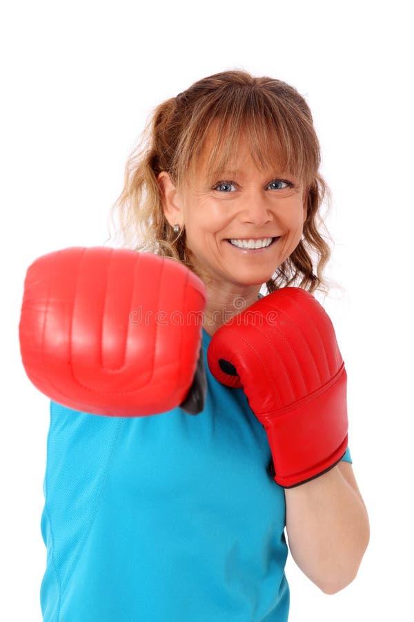 Blonde reife Frau mit dem Boxhandschuhlochen stockfotos