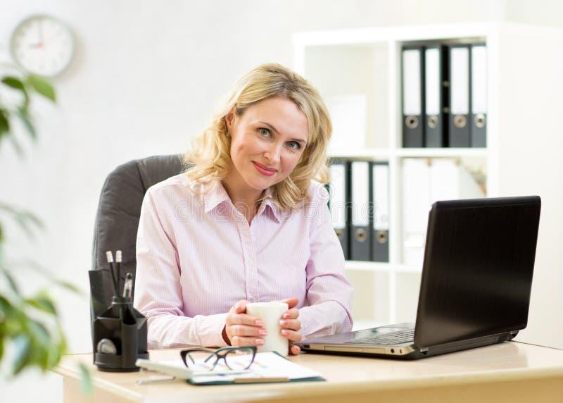 Blonde reife Geschäftsfrau, die an Laptop und trinkendem Kaffee arbeitet lizenzfreies stockbild