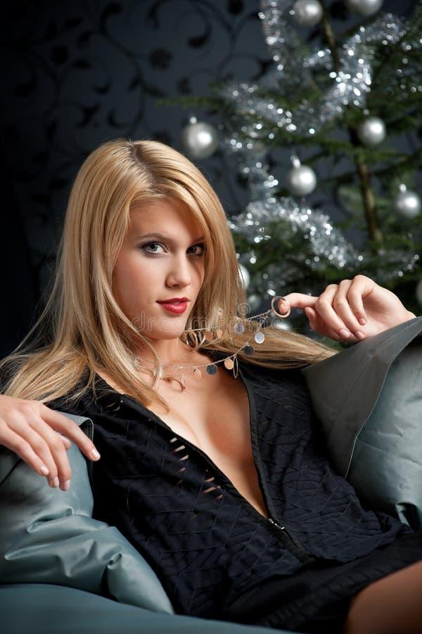 Blonde reizvolle Frau im schwarzen Kleid auf Weihnachten lizenzfreies stockbild