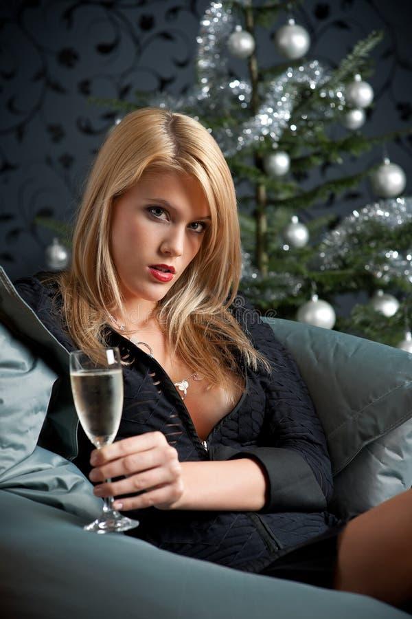 Blonde reizvolle Frau mit Champagner auf Weihnachten lizenzfreie stockbilder
