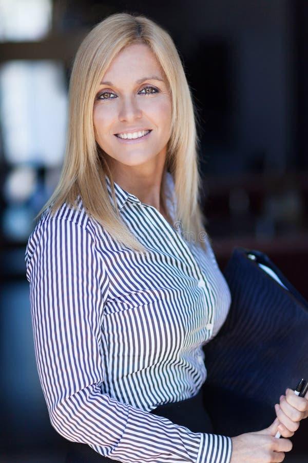 Blonde rijpe onderneemster die bij de camera glimlachen Bureauachtergrond Zij houdt een document royalty-vrije stock foto's