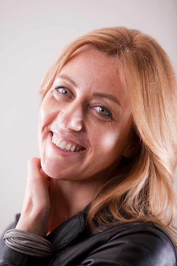 Blonde rijpe vrouw die in zwart leer glimlachen royalty-vrije stock foto