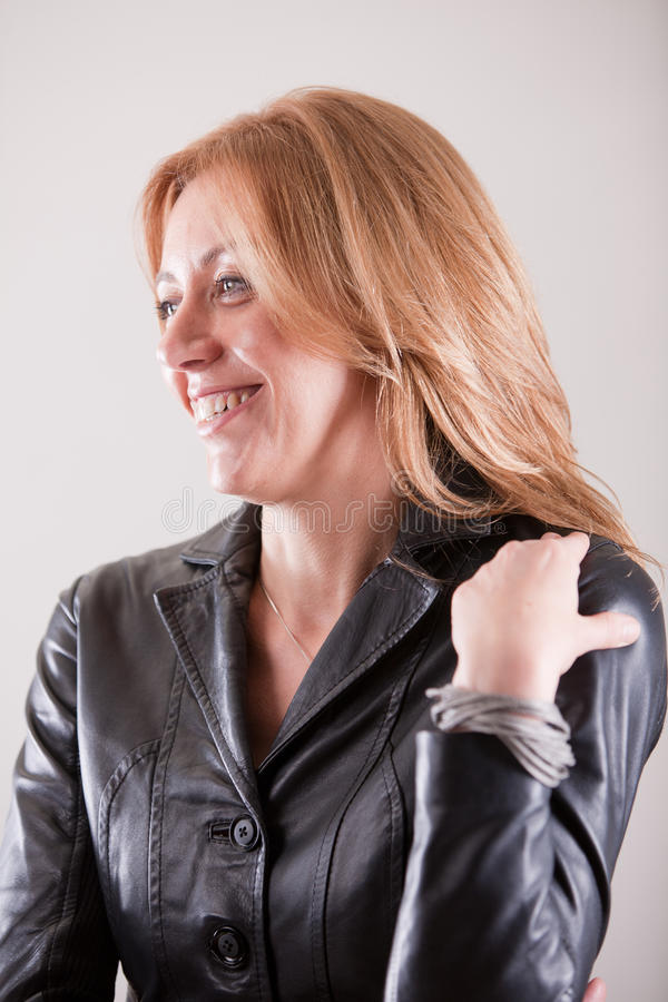Blonde rijpe vrouw die in zwart leer glimlachen royalty-vrije stock fotografie