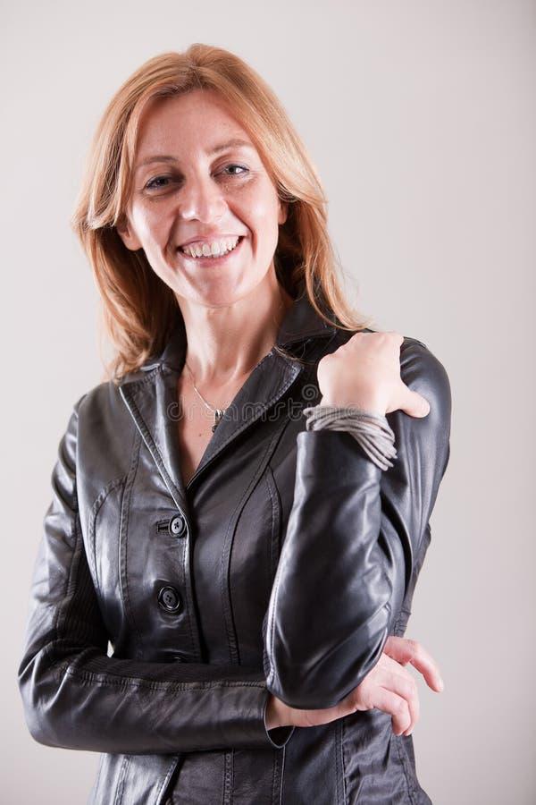 Blonde rijpe vrouw die in zwart leer glimlachen stock foto's