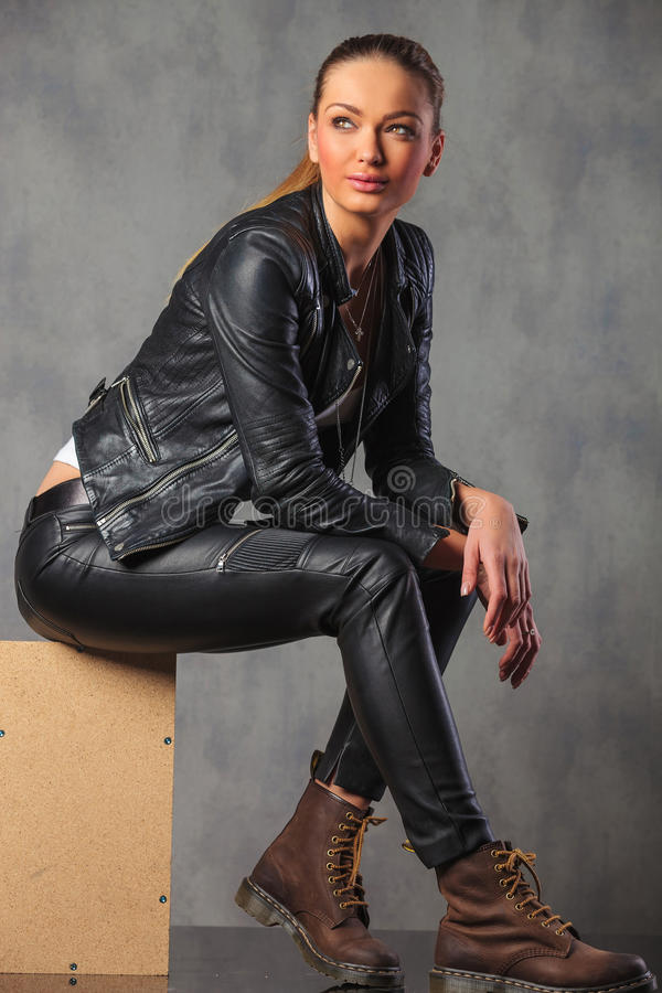 Blonde rocker in leather posing smiling seated stock image