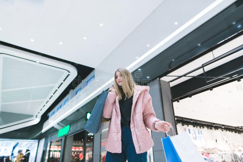 The blonde`s affair with packages goes around a modern shopping mall and makes purchases stock photography